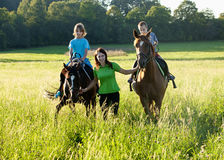 Woman Leading Two Horses with Boys Stock Image