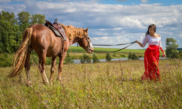 Woman leads the horse. Walk with a horse on nature Royalty Free Stock Photography