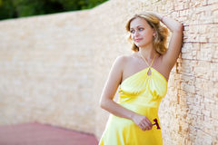 Woman leaned against the wall and holding a flower Stock Photo