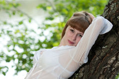 The woman leaned the elbows on a tree. The beautiful young woman in a white shirt leaned the elbows on a tree Stock Photos
