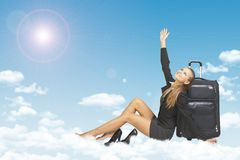 Woman leaned on luggage bags. Clouds, sky, sun as Stock Photo