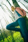 Woman leaning. Young female leaning by tree in forest, low angle view, smiling Royalty Free Stock Photography