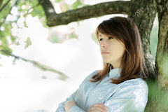 A woman leaning against a big tree alone in the park. She thought about an important problem Stock Image