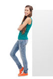 Woman leaning against blank billboard Stock Photo