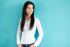 Woman leaning against a blue wall Royalty Free Stock Photos