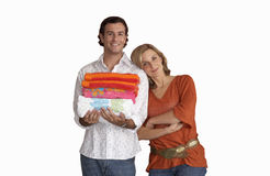 Woman leaning against boyfriend, man holding pile of folded towels, smiling, front view, portrait, cut out. Woman leaning against boyfriend, men holding pile of royalty free stock photography