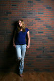 Woman leaning against brick wall Stock Image