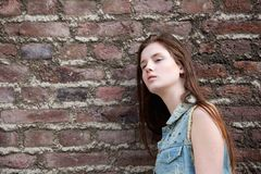 Woman leaning against brick wall Royalty Free Stock Images