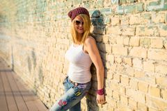 Woman leaning against brick wall. Hipster woman leaning against brick wall royalty free stock images