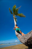 Woman leaning against coconut tree by a tropical b Stock Images