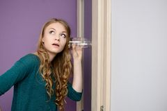 Woman leaning against door listening to a conversation using glass. Stock Photography