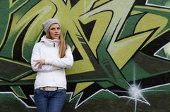 Woman leaning against graffiti wall Royalty Free Stock Image
