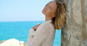 Woman Leaning Against Rock Wall By Windy Ocean stock footage