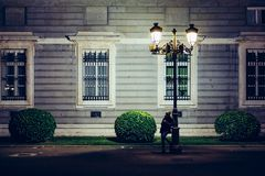 Woman leaning against street light at night Stock Photography