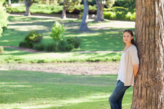 Woman leaning against a tree in the park Royalty Free Stock Image
