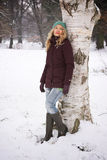 Woman leaning against tree in winter Royalty Free Stock Photos
