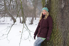 Woman leaning against tree in winter landscape Stock Image