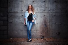 Woman leaning against wall Stock Photo