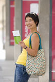 Woman leaning against wall holding ticket, smiling, portrait, side view Royalty Free Stock Photo