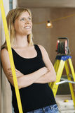 Woman Leaning Against Wall With Ladder Behind Royalty Free Stock Photography