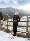Woman leaning against wooden fence on highland farm in Alps Royalty Free Stock Photos