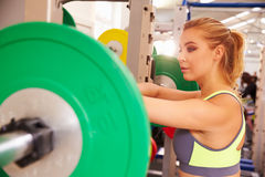 Woman leaning on a barbells at a squat rack in a gym Royalty Free Stock Images
