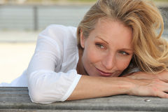 Woman leaning on a bench Royalty Free Stock Images
