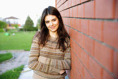 Woman leaning on the brick wall Royalty Free Stock Image