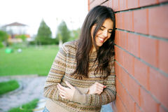 Woman leaning on the brick wall Stock Photo