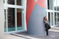 Woman leaning on a building column Royalty Free Stock Photo