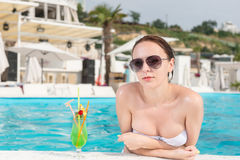 Woman Leaning on the Edge of the Pool with Drinks Royalty Free Stock Images