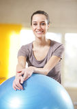 woman leaning on an exercise ball at the gym Royalty Free Stock Images