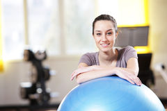 woman leaning on an exercise ball at the gym Royalty Free Stock Photo