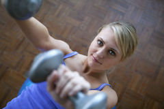 Woman leaning on a fitness ball lifting weights Stock Photography