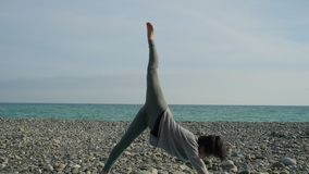 Woman is leaning on floor by hands and lifting leg up, doing yoga asana outside stock footage