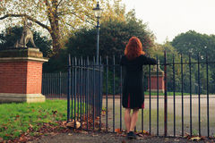 Woman leaning on gate in park Royalty Free Stock Photography