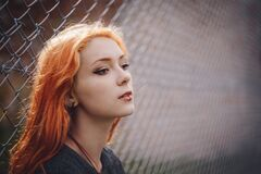 Woman Leaning on Gray Chain Link Fence Royalty Free Stock Images