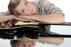 Woman leaning on a guitar. Young woman leaning on a guitar Royalty Free Stock Photography