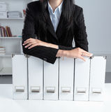 Woman leaning on her arms on top of document folders Stock Photos