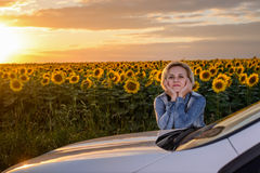 Woman leaning on her car waiting at sunset Stock Photos