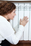 Woman leaning his hand and cheeks to radiator. Woman leaning his hand and cheeks to central heating radiator stock images