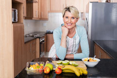 Woman leaning kitchen counter. Happy middle aged woman leaning against the kitchen counter royalty free stock photo