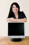 Woman leaning on lcd screen. Smiling businesswoman leans on an lcd computer screen Royalty Free Stock Photography
