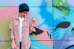 Woman Leaning on Multicolored Wall stock images