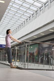 Woman Leaning Off Railing In Shopping Centre Stock Photo