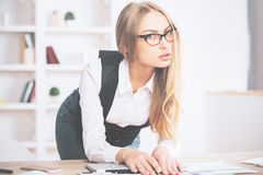 Woman leaning on office desk. Portrait of attractive young woman leaning on office desk with laptop and paperwork Stock Image