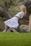 Woman leaning on olive tree trunk with eyes closed Royalty Free Stock Images