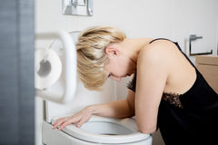 Woman leaning on open toilet seat at indoor bathroom Royalty Free Stock Images