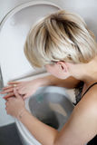 Woman leaning on open toilet seat at indoor bathroom Royalty Free Stock Photography