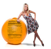 Woman Leaning on Orange with Nutrition Label Stock Photography